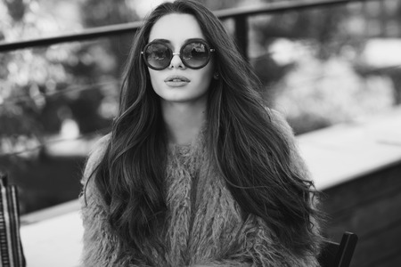 Trendy drssed fashionable girl wearing fur coat. Young pretty beautiful woman with long curly hair looking at you.
