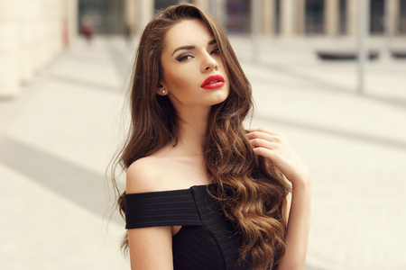 stylish hair: Closeup face fashion portrait of young beautiful pretty stylish girl with long curly brunette hair and red lips posing in city Stock Photo