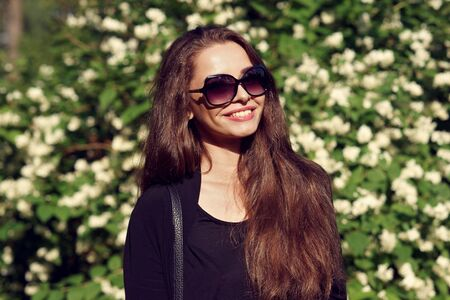 ttractive: Happy smiling girl posing against green bushes with white blooming flowers. Stylish girl wearing black blouse and sunglasses Stock Photo