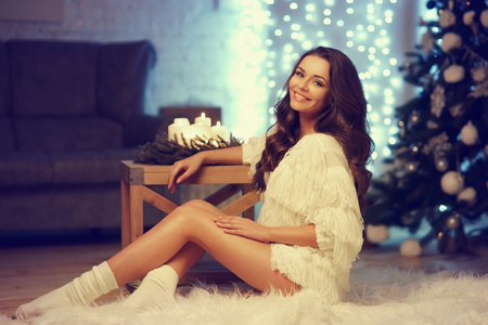 Happy joyous girl with long curly hair sitting on white fur carpet agaist bokeh lights, cristmas tree and sofa