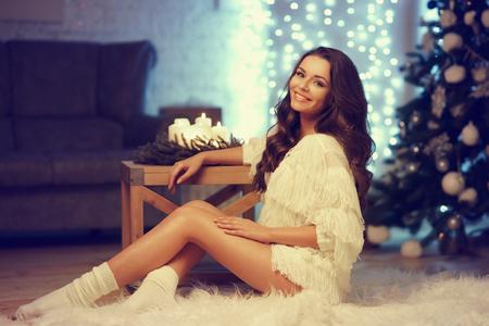 Gelukkig vreugdevolle meisje met lang krullend haar zitten op wit bont tapijt agaist bokeh lichten, cristmas boom en een bank