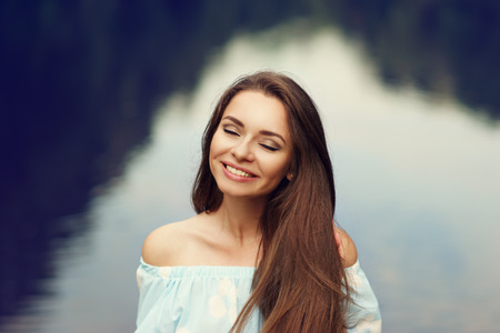 Happy joyful young woman in light blue summer dress closeup portrait outdoors in park against water background in bokeh. Smiling girl.