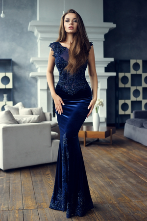 Gorgeous tall slim glamorous woman in long blue lace luxury evening dress standing in lounge interior with wooden floor. Brunnette beautiful stunning girl looking at you. Vogue style portrait Stockfoto