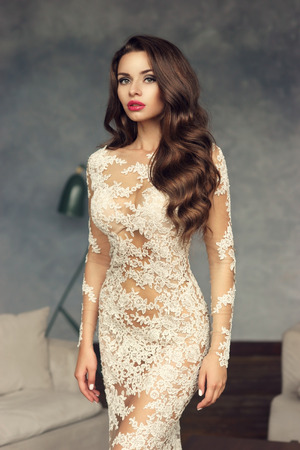 Young stunning sexy woman with long brunette curly hairm make up and red lips standing and posing in loft lounge interior and looking at you. Foto de archivo