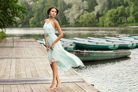 여름 날에 목조 부두에서 걷고 밝은 파란색 드레스 예쁜 여자