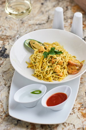 Flat egg noodles with seafood Stock Photo