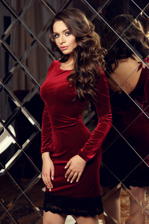 Calm sensual girl with long curly brown hair and makeup posing against large mirror in red silk velvet dress Stockfoto