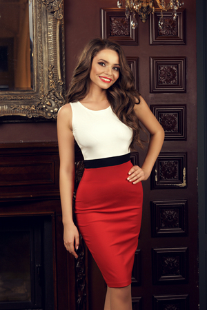 Pretty beautiful sexy woman in red and white sheath cocktail dress posing in luxury interior and standing near wooden panel wall. Stock Photo