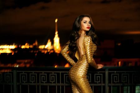 セクシーなファッショナブルな美しい若い女性長い黄金輝くイブニング ドレス立ってボケで夜の街の明かりのビュー上のバルコニーで。長い巻き毛 写真素材