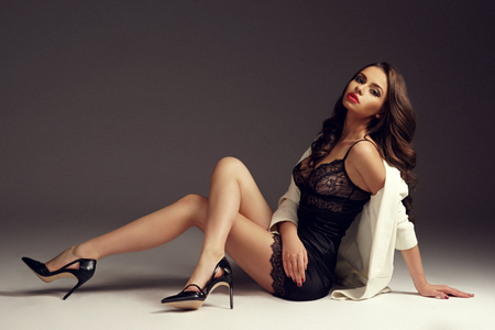 Young sexy girl in black nightie, high heels and white coat sitting on floor. Fashion style vogue portrait of brunette woman with long curly hair. Фото со стока