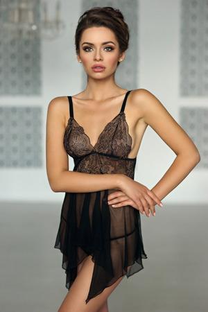 Romántico hermosa y sexy mujer de pie y posando en el interior de la habitación de lujo brillante, vistiendo lencería de encaje negro sensual. Foto de archivo - 77514169