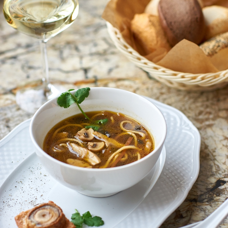 white wine: Asian cuisine. Mushroom soup with egg noodles served with toast, bread and white wine on marble background.