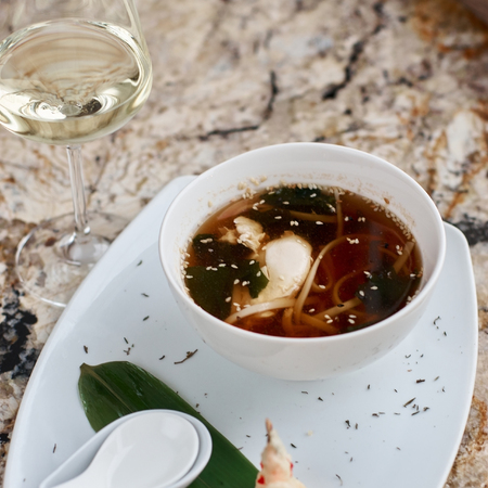Japanese cuisine. Noodle soup udon in white ceramic bowl served with spoon, glass of white wine and king prawn on marble table Stock Photo