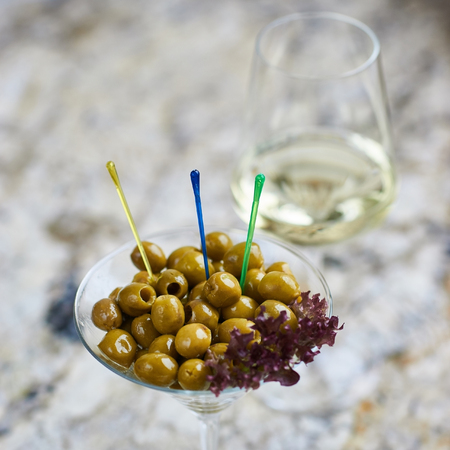 white wine: Appetizer. Green olives served in martini glass with glass of white wine on marble table