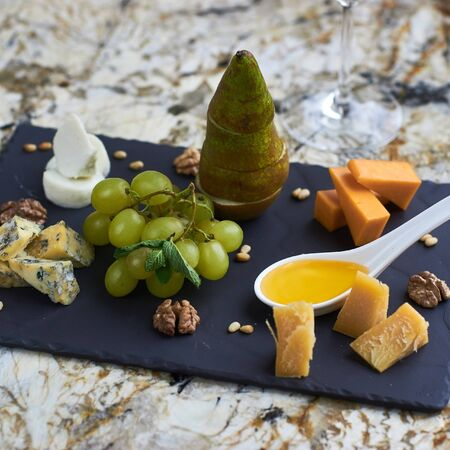 white wine: Cheese plate with fresh fruits served on black ceramic board on marble table