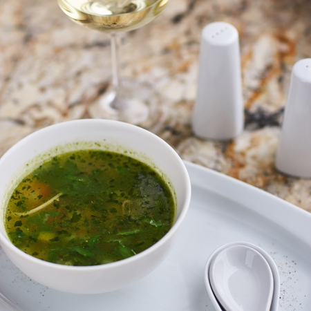 white wine: Minestrone soup with arugula served in a white bowl with ceramic spoon, glass of white wine on marble table Stock Photo