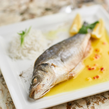 Whole boiled wolffish served with sauce from lemon butter and white wine on square white plate