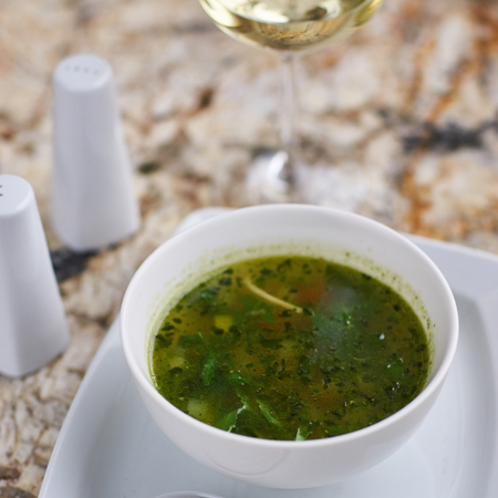 green bean: Minestrone soup with arugula served in a white bowl with ceramic spoon, glass of white wine on marble table Stock Photo