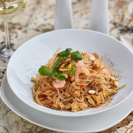 korean salad: Rice noodles with peanuts, chicken and shrimps served on white round plate with glass of white white on marble table Stock Photo