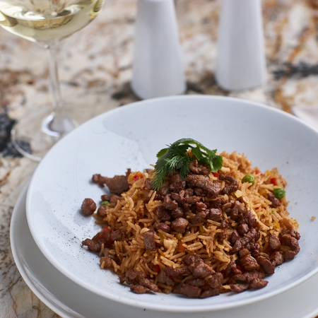 white wine: Fried rice with beef slices served in white round plate with glass of white wine on marble table Stock Photo