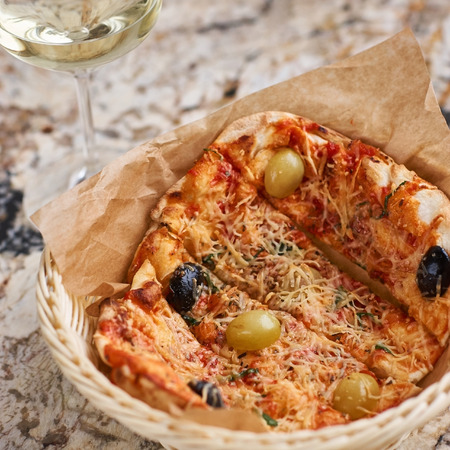white wine: Hot Tandoori Focaccia with tomato Concasse, grapes and parmesan cheese in wicker basket with glass of white wine on marble table Stock Photo