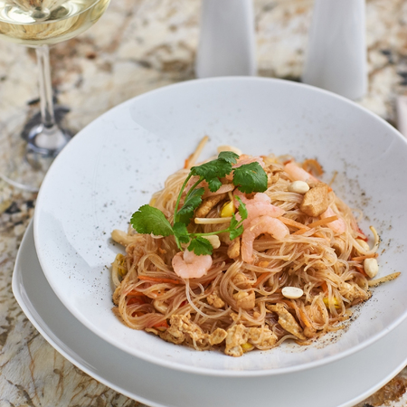 Rice noodles with peanuts, chicken and shrimps served on white round plate with glass of white white on marble table Stock Photo