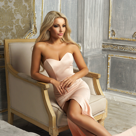 Elegant lady with long curly blonde hair wearing slit mermair dress sitting in armchair in luxury interior. Fashion style portrait.