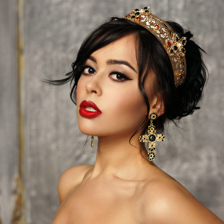 Closeup beauty portrait of young beautiful brunette woman with hairstyle, crown and earrings. Fashion girl.
