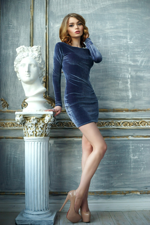 velvet dress: Fashionable portrait of young red hair woman in blue dress standing in luxury interior