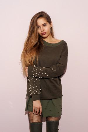 Ziemlich stilvolles Mädchen in Sweatshirt, Sackzeug Stiefel, Gitter Strumpfhosen und Rock stehen in der Nähe von rosa Wand