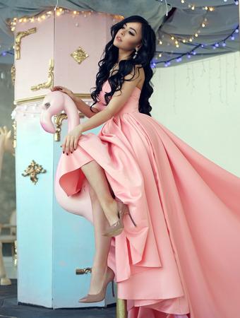 Mode-Mode-Stil-Porträt. Elegante Dame mit dem lockigen Haar des Brunette im rosa Ballkleid am Karussell. Standard-Bild - 78884496