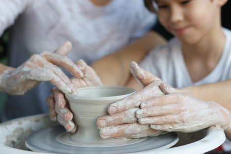 sculp: Parents teach their child to work on potter wheel. Father showing how to sculp clay pot. Closeup of dirty hands. Shallow DOF.