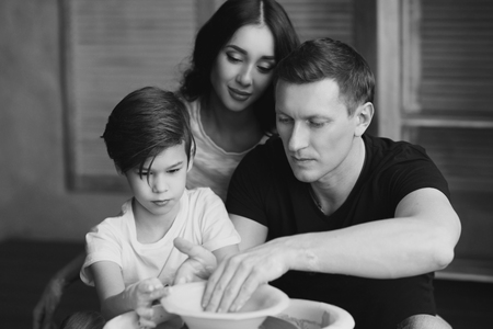 Young caucasian family working on potters wheel. Handsome father, beautiful mother and young son. Pottery classes. Dirty Hands. Parents enjoying time together with their child.