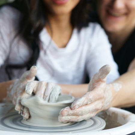 Happy smiling joyful romantic couple working together on potter wheel and sculpting clay pot. Focus on dirty hands