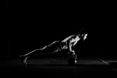 Fitness training. Man doing push ups exercise using dumbbells or weights in dark gym.