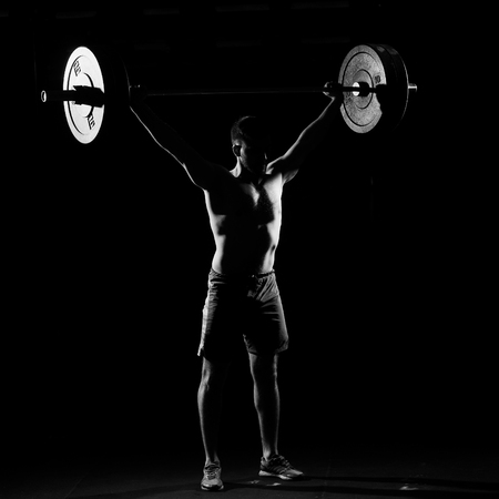 Fitness training. Man standing with barbell in dark gym. Stock Photo