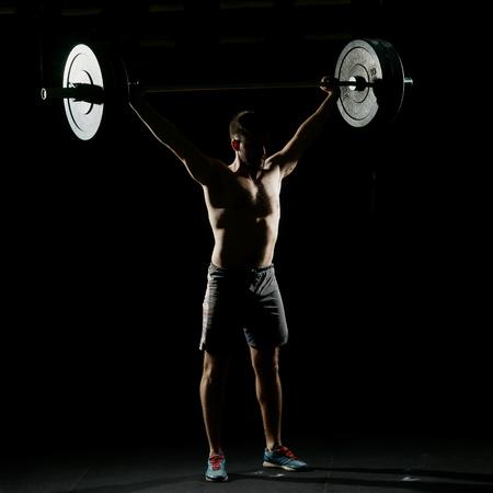 フィットネス ・ トレーニング。暗いジムでバーベルで立っている男。