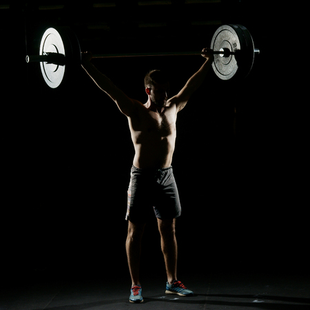 Fitness training. Man standing with barbell in dark gym. Imagens