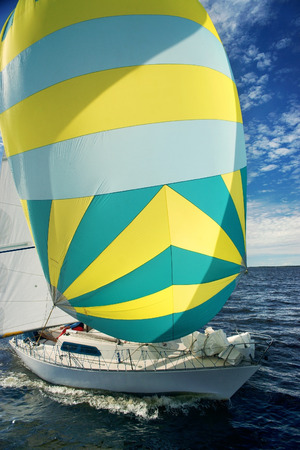 spinnaker: Yachting race. Sailing regatta. Yachts with colorful yellow green gray spinnaker in the sea on sunny windy day Stock Photo