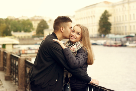Happy joyful beautiful young romatic couple hugging and cuddling at city street on autumn or spring day Stock Photo