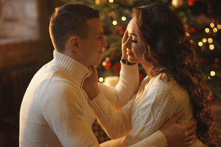 pullovers: Young couple staying at home together on holiday evening and sitting on floor in front of christmas tree and hugging. Cute romantic lovers in white pullovers