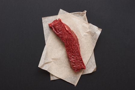 cut paper: Slice of fresh beef meat lying on bakers paper on black background Stock Photo