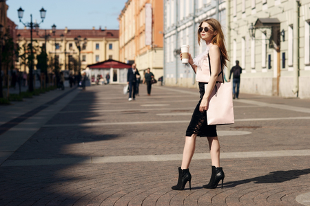 Young beautiful caucasian girl with shopping bag walking in the city on a sunny summer day. Pretty woman with long red hair wearing black skirt and pink blouse