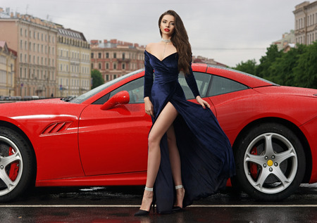 Glamorous fashionable woman with long legs in blue evening dress and long brown hair standing against red sport car at city street on overcast day