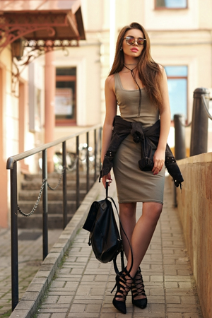 Young beautiful stylish woman wearing green dress, black jeans jacket and sunglasses walking at the street in city. Pretty brunette girl with long hair holding backpack