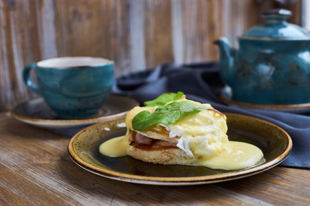 benedict: Breakfast. Eggs Benedict on plate, teapotand cup of hot black tea on wooden table. Stock Photo