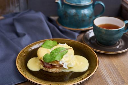 benedict: Breakfast. Juicy Egg Benedict Brunch. Hot black tea. Cup. Teapot. Wooden table.