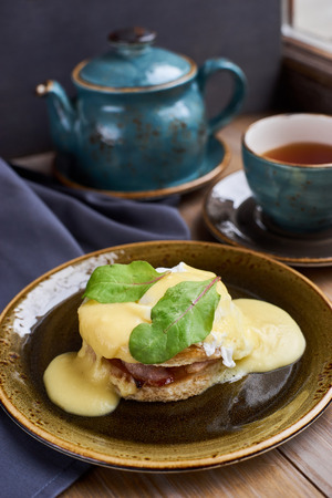 benedict: Breakfast. Delicious eggs benedict served on plate. Teapot and cup of hot black tea.