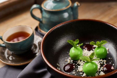 Small green apples desert with chocolate, mint leafs and caramel served in big black plate. Hot black tea.