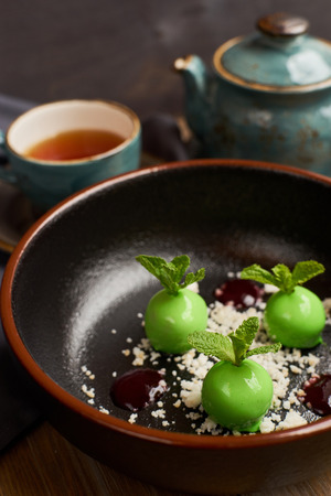 Chefs dessert from apples, chocolate, mint and caramel glazed in form of small apples with leafs. Served with teapot and cup of hot black tea.